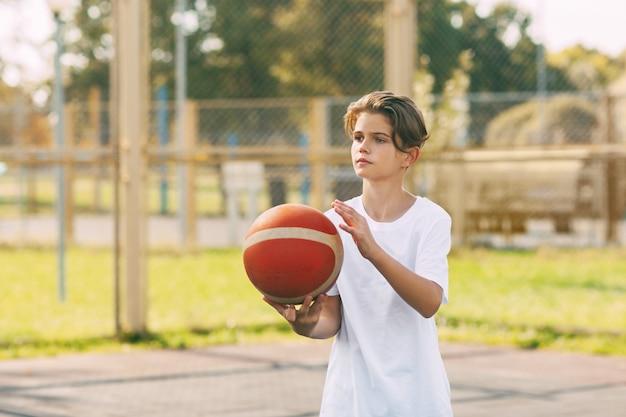 Ein schöner teenager in einem weißen t-shirt steht auf dem basketballplatz und hält einen basketball