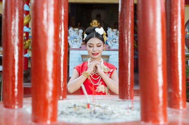 Ein schönes asiatisches mädchen, das eine rote anbetung trägt