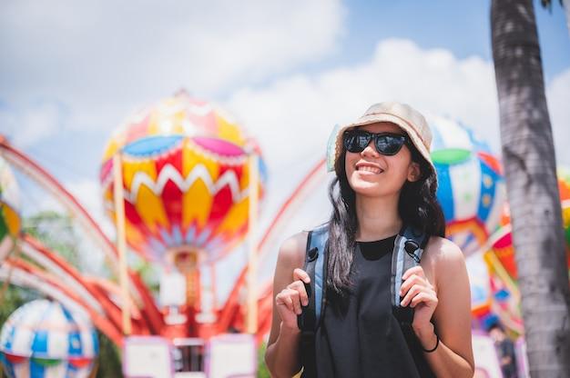 Ein schönes asiatisches mädchen genießt ihren urlaub im vergnügungspark an einem sonnigen tag, schöner klarer himmel, frauen mit sonnenbrille, lächelndes mädchen, glücklicher urlaub