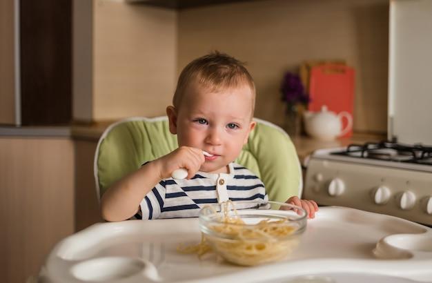 Ein schönes baby schaut in die kamera und hält eine gabel in der hand. ein kleiner junge lernt mit einer gabel makkaroni zu essen.