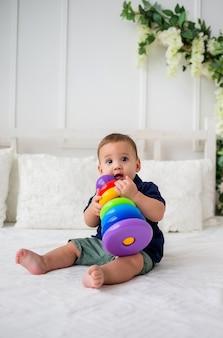 Ein schönes baby sitzt auf einem weißen bett und spielt mit einem pyramidenspielzeug