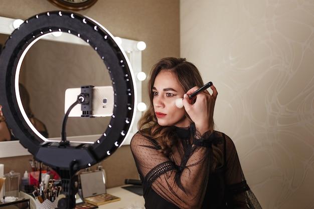 Ein schönes blogger-mädchen schminken sich vor einer großen lampe im gesicht und dreht für ihre zuschauer ein video auf ihrem handy.