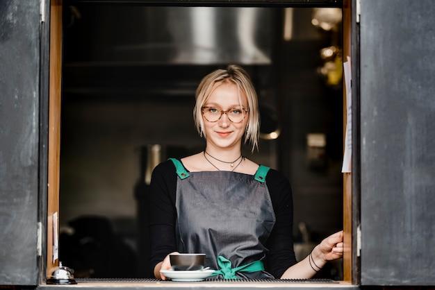 Ein schönes blondes junges barista-mädchen, das eine tasse kaffee in einem café zum mitnehmen serviert.
