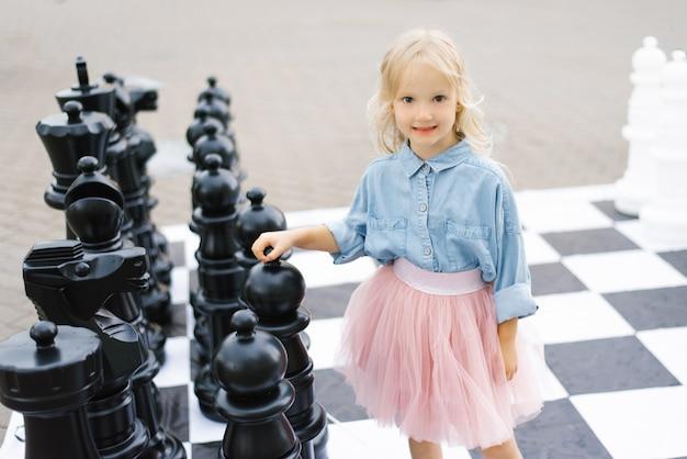 Ein schönes blondes mädchen von fünf jahren steht neben einem großen schachspiel im park