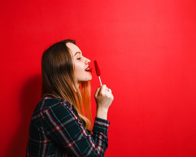 Ein schönes brunettemädchen mit einer süßigkeit in ihrer hand, die spaß auf einem roten hintergrund hat.