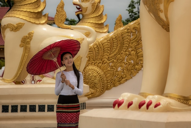 Ein schönes burmesisches mädchen trägt eine tracht für einen spaziergang in der shwedagon-pagode von yangon, myanmar.