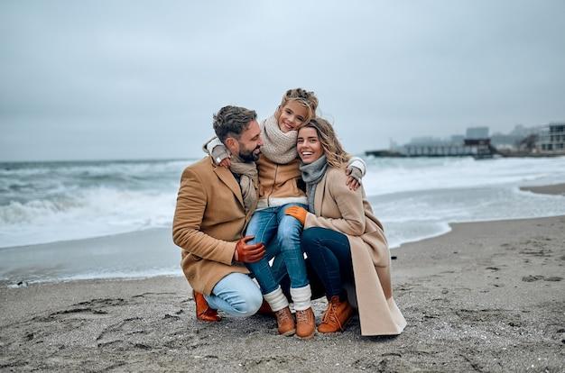 Ein schönes ehepaar und ihre schöne tochter umarmen sich an der küste und tragen im winter mäntel.