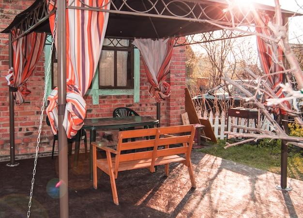 Ein schönes erholungsgebiet für eine familie in einem landhaus, ein zelt mit einer bank und einem tisch auf dem hintergrund eines backsteinhauses mit fenstern und dach, frühling, sonnenuntergang
