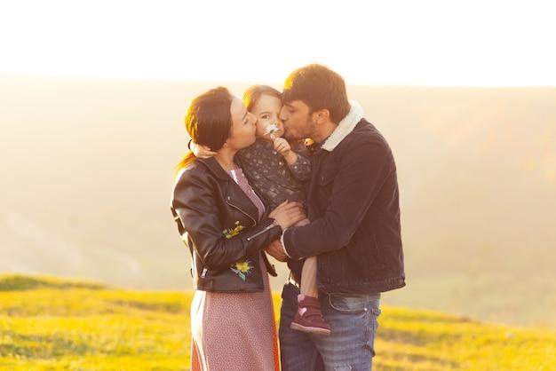 Ein schönes foto einer jungen familie, die in einem feld steht, das spaß hat