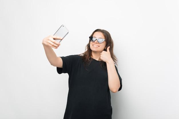 Ein schönes foto einer jungen frau, die ein selfie mit sonnenbrille macht, während sie einen lächelnden daumen nach oben hält