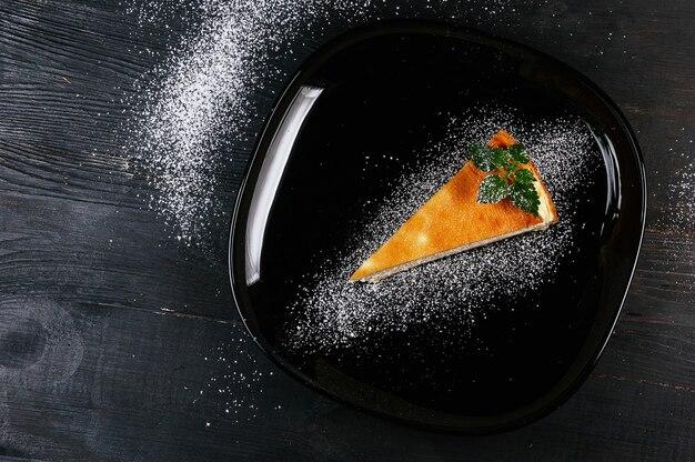 Ein schönes foto von einem stück kuchen auf einem schwarzen pulverteller