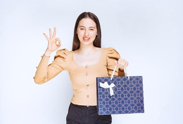 Ein schönes frauenmodell mit einer einkaufstasche, die ok geste zeigt.