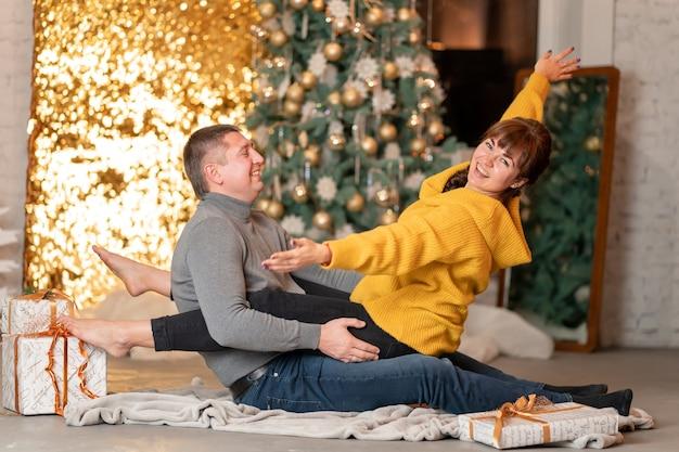 Ein schönes fröhliches paar begrüßt die weihnachtsferien in einer gemütlichen häuslichen atmosphäre