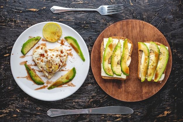 Ein schönes gesundes romantisches frühstück von spiegeleiern in form eines herzens auf einem weißen teller und avocado-sandwiches