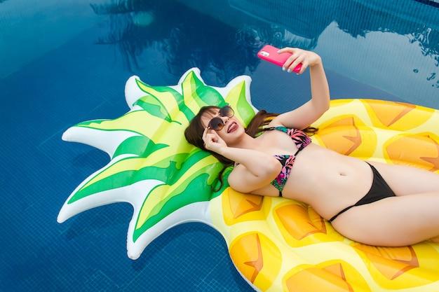 Ein schönes glückliches mädchen, das ein selfie mit ihrer sonnenbrille hält und ihre zunge herausstreckt, die auf ihrem schwimmer im pool liegt.