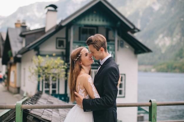 Ein schönes hochzeitspaar geht auf der straße nahe dem see in einer feenhaften österreichischen stadt