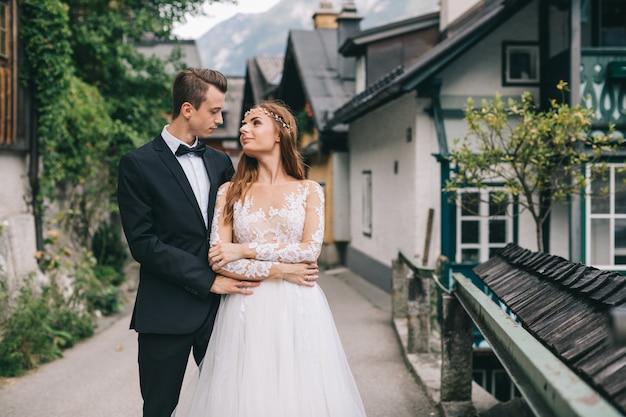 Ein schönes hochzeitspaar geht in eine feenhafte österreichische stadt, hallstatt.