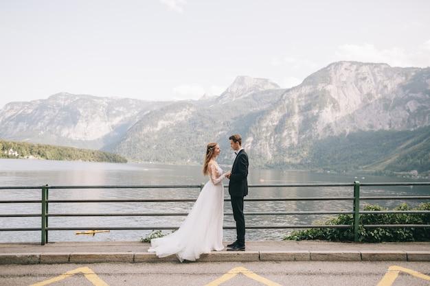 Ein schönes hochzeitspaar geht nahe einem see in einer feenhaften österreichischen stadt, hallstatt.