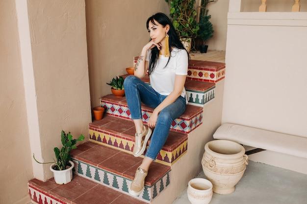 Ein schönes junges asiatisches brünettes mädchen in jeans und einem weißen t-shirt sitzt auf den stufen mit einem muster.