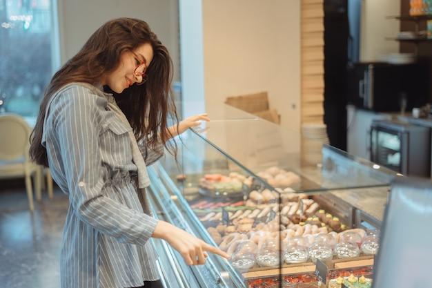 Ein schönes junges asiatisches mädchen mit langen haaren wählt ein dessert in einem café am fenster. schönes interieur des bäckerei-cafés