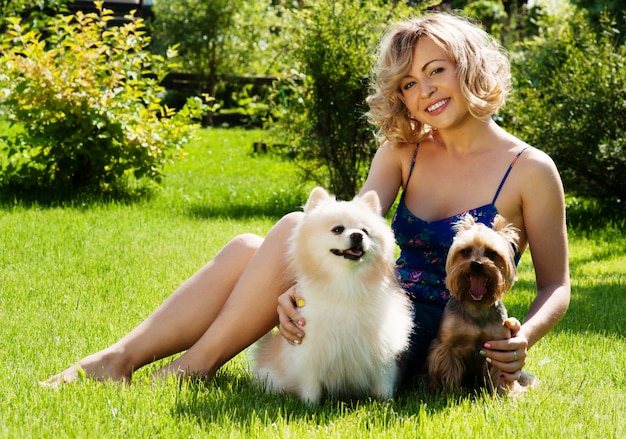 Ein schönes junges blondes mädchen im park mit hunden