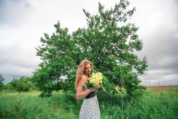 Ein schönes junges blondes mädchen sammelte einen strauß wildblumen. genießen sie einen spaziergang an einem warmen sommertag.