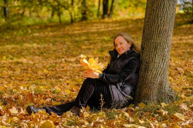 Ein schönes junges blondes mädchen sitzt auf gefallenem herbstlaub im park