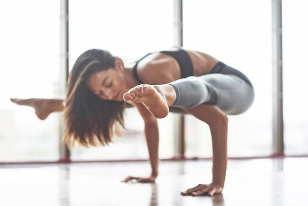 Ein schönes junges brünettes mädchen führt verschiedene yoga-strecken durch.