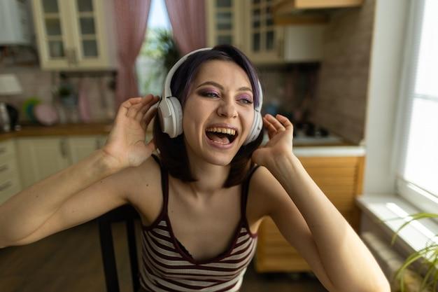 Ein schönes junges brünettes mädchen in der küche zu hause arbeitet an einem laptop und hört musik über kopfhörer