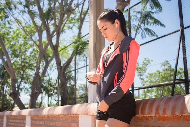 Ein schönes junges fitnessmädchen, das ihre jacke im park schließt