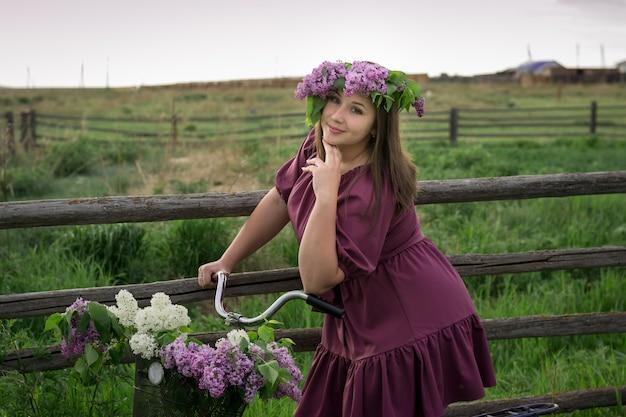 Ein schönes junges kaukasisches lächelndes glückliches mädchen im lila kleid in einem kranz und mit einem fahrrad ein korb des blühenden flieders in der landschaft. modell plus größe. frühling im rustikalen stil. reif aus blumen