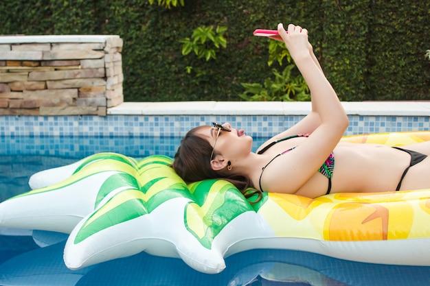 Ein schönes junges mädchen, das ein selfie macht und ihre zunge herausstreckt, das auf ihrem schwimmer im pool liegt.