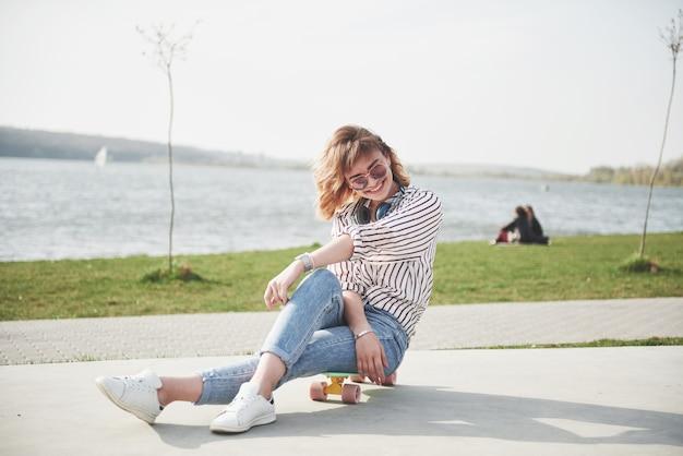 Ein schönes junges mädchen hat spaß im park und fährt skateboard.