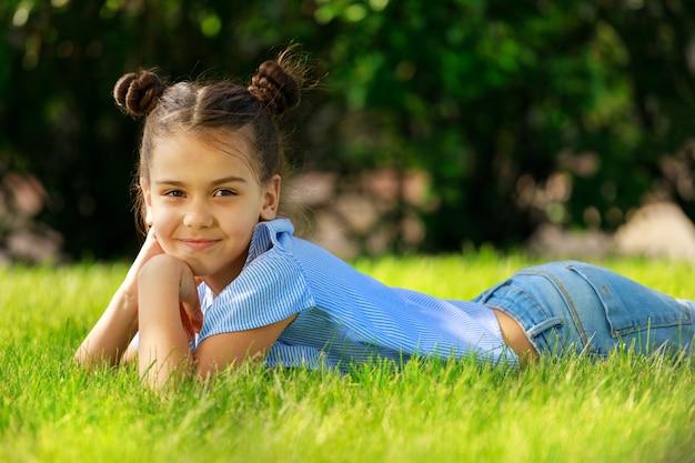 Ein schönes junges mädchen in blauer bluse und jeans liegt im sommer im park auf dem gras. foto in hoher qualität