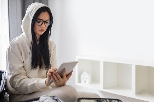 Ein schönes junges mädchen in einem weißen freizeitanzug sitzt auf dem bett und benutzt ein tablet