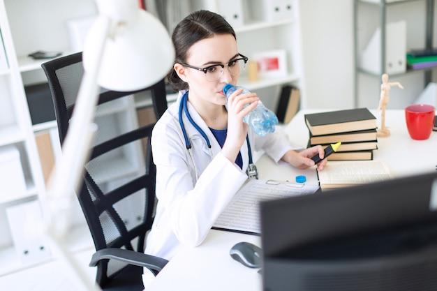 Ein schönes junges mädchen in einer weißen robe sitzt an einem computertisch, trinkt wasser und betrachtet den monitor.