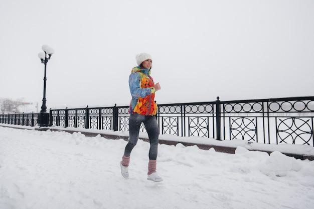 Ein schönes junges mädchen joggt an einem frostigen und schneereichen tag. sport, gesunder lebensstil.
