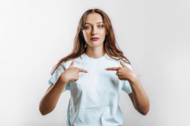 Ein schönes junges mädchen lächelt und zeigt mit den fingern auf sich selbst auf einem weißen, isolierten grauen hintergrund. platz für werbung. positive frau mit mode-make-up mit lila lippen.