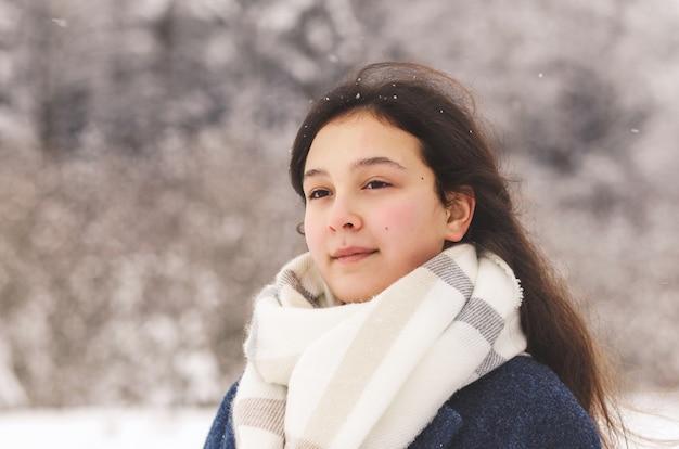 Ein schönes junges mädchen schaut in der ferne in die natur des winters. nachdenklichkeit und verträumtheit