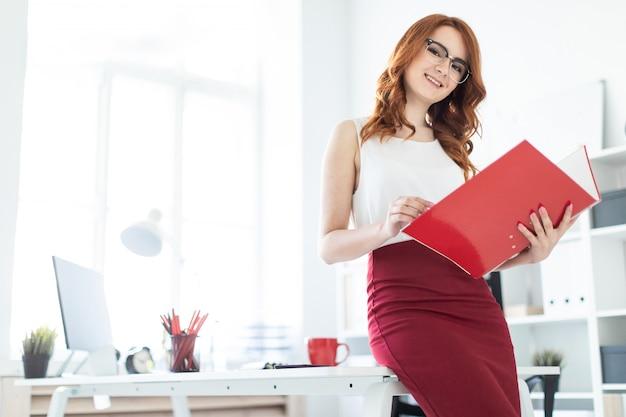 Ein schönes junges mädchen setzte sich auf den tisch im büro und hielt eine rote mappe in der hand.