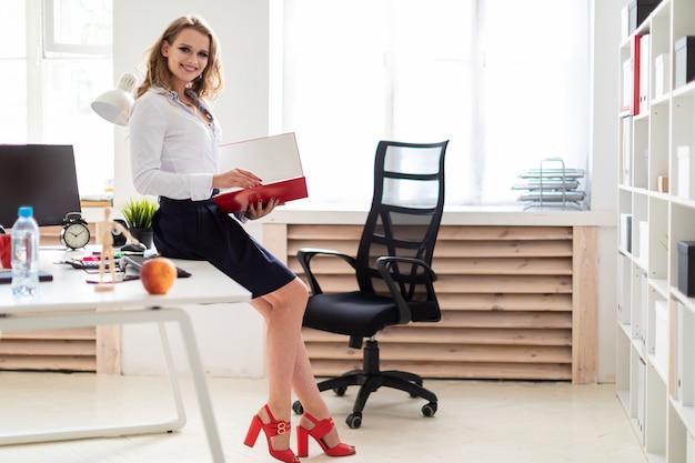 Ein schönes junges mädchen setzte sich auf den tisch im büro und hielt einen ordner mit dokumenten in der hand.