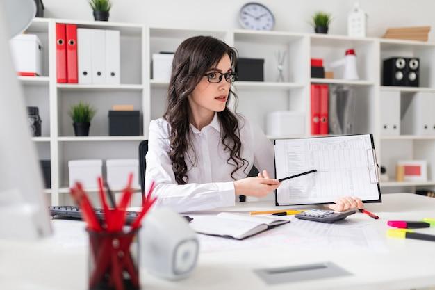 Ein schönes junges mädchen sitzt an einem tisch im büro und zeigt mit einem bleistift auf die informationen im dokument.