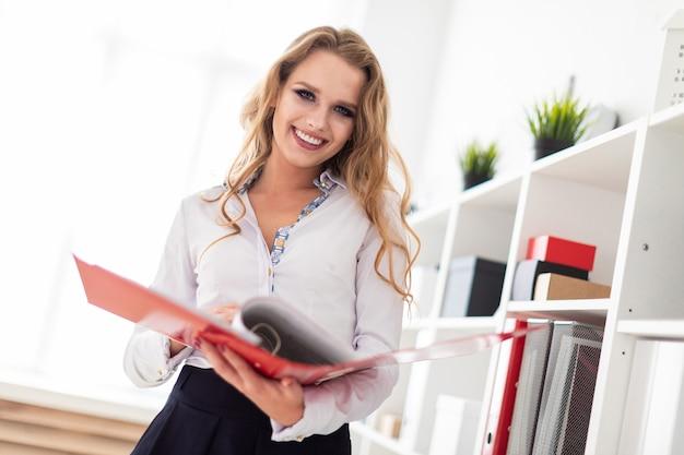 Ein schönes junges mädchen steht in der nähe eines gestells im büro und hält einen ordner mit dokumenten.