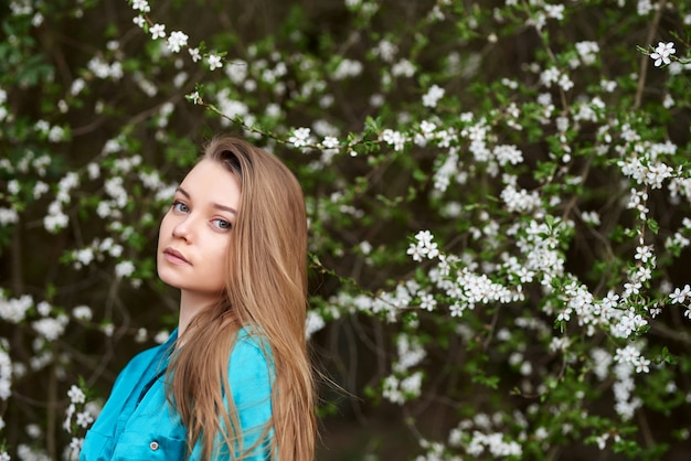 Ein schönes junges mädchen steht zwischen den blühenden bäumen. weiße blumen. frühling.