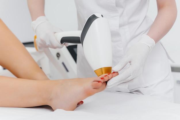 Ein schönes junges mädchen wird in einem spa-salon mit moderner ausrüstung einer laser-haarentfernung unterzogen. schönheitssalon. körperpflege.