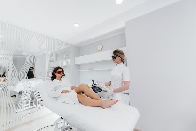 Ein schönes junges mädchen wird in einem spa-salon mit moderner ausrüstung einer laser-haarentfernung unterzogen