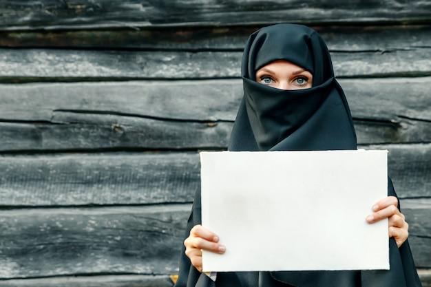 Ein schönes, junges, moslemisches mädchen in einem schwarzen schleier mit einem geschlossenen gesicht gegen einen grauen baum. in handsa blatt papier. copyspace.