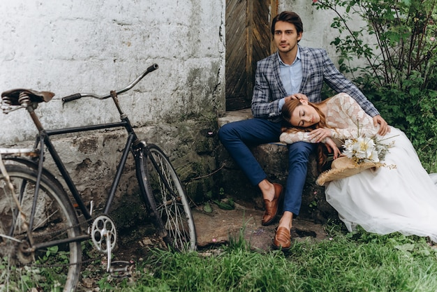 Ein schönes junges paar braut und bräutigam mit einem fahrrad in der nähe von alten haus