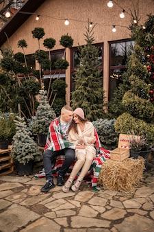 Ein schönes junges paar in weißen kleidern sitzt neben einem weihnachtsbaum im garten. glücklicher mann und frau, romantik, weihnachtsfeier, spaß, liebe.