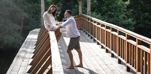Ein schönes junges paar kommuniziert auf einer brücke im wald, ein date in der natur, liebesgeschichte. Premium Fotos